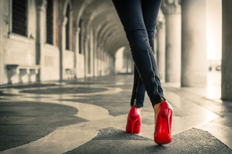 Woman in black leather pants and red high heel shoes