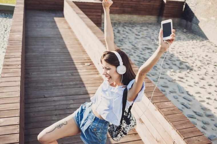 Emotional young woman with headphones listening music outdoors, summer girl portrait