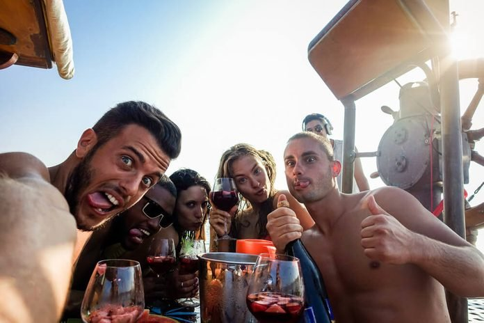 Happy friends taking selfie photo with mobile phone camera in boat party - Young people having fun in ibiza drinking champagne sangria - Summer vacation concept - Warm filter
