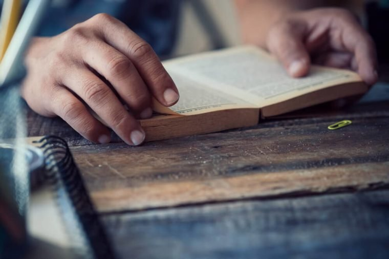 side view of man reading the bible in the darkness over wooden table.vintage effected photo.