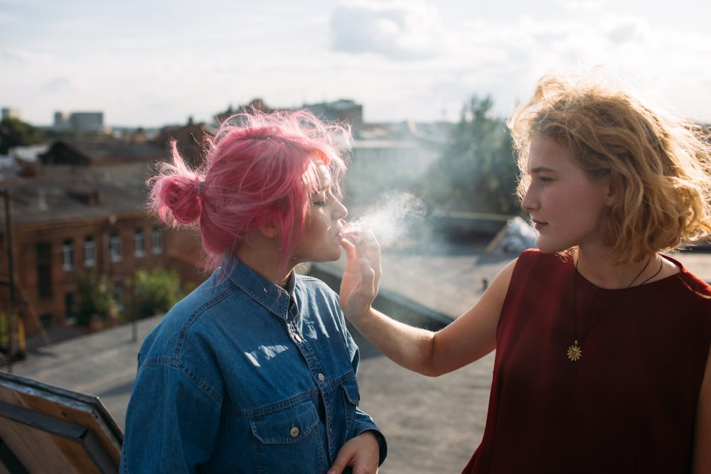 Bad influence. Girl smoking a cigarette from her friend's hand. Street teenage lifestyle. Dangers of bad associations