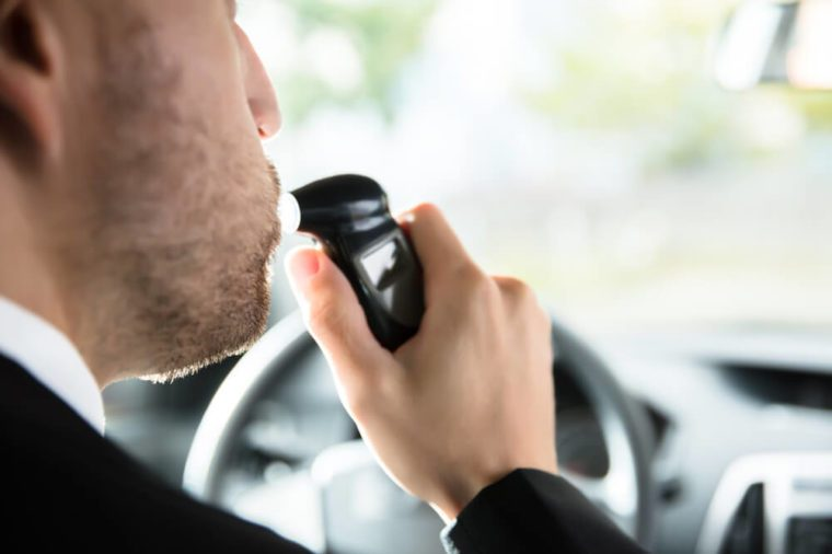 Close-up Of A Man Sitting Inside Car Taking Alcohol Test