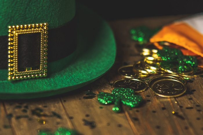 Green leprechaun hat with black belt and buckle next to gold dust and coins with glitter shamrocks and an Ireland flag representing the Catholic spring holiday of Saint Patrick. St Patrick's Day fun facts.