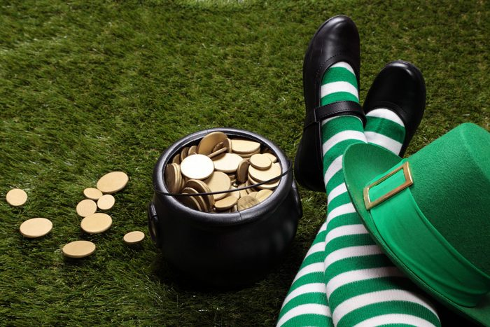 Female Leprechaun on the grass next to a pot of gold. st patricks day fun facts.