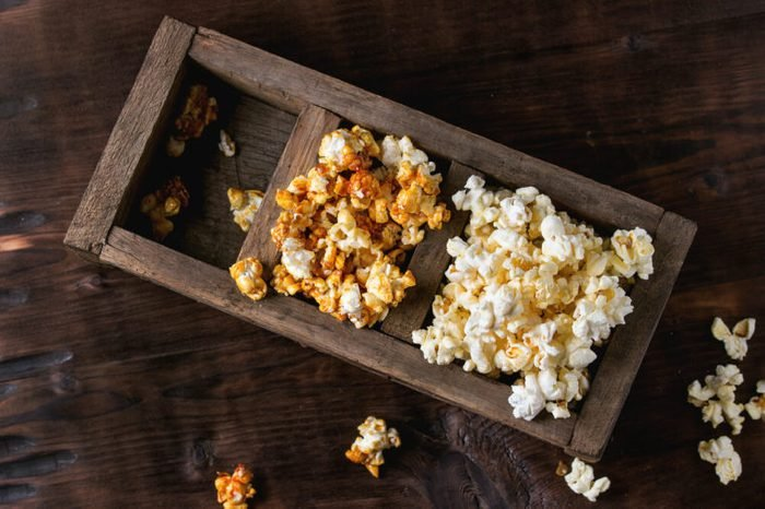 Prepared salted and caramelized sweet popcorn in old wood three sectioned box over dark textured wooden background. Top view. With space for text