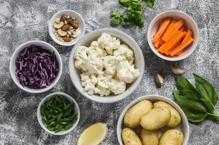 Variety of fresh vegetables in bowls - potatoes, red and cauliflower cabbage, spinach, green onions, carrots, nuts, olive oil, cilantro. Raw ingredients. Vegan table. Top view