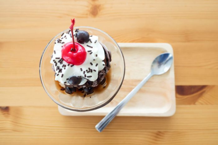 Chocolate sundae ice cream served with whipping cream and cherry on top. Pour chocolate sauce and chocolate ball. On wooden tray. Top view.