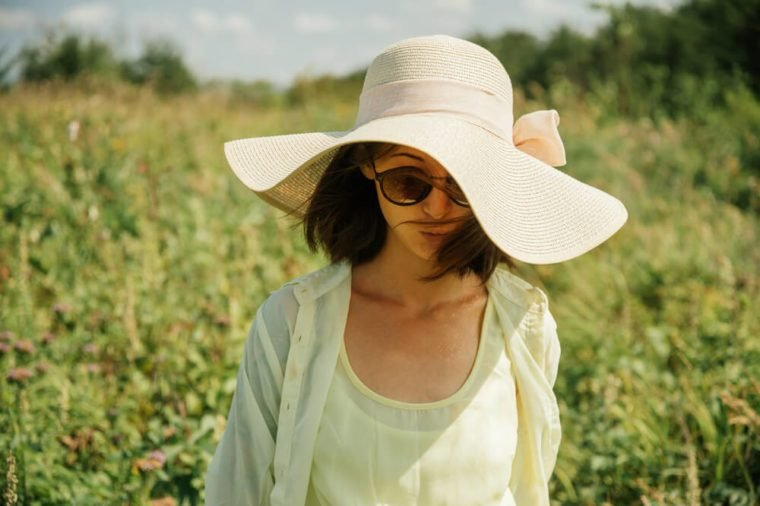 Beautiful woman in sunglasses and hat with wide brim on nature in summer