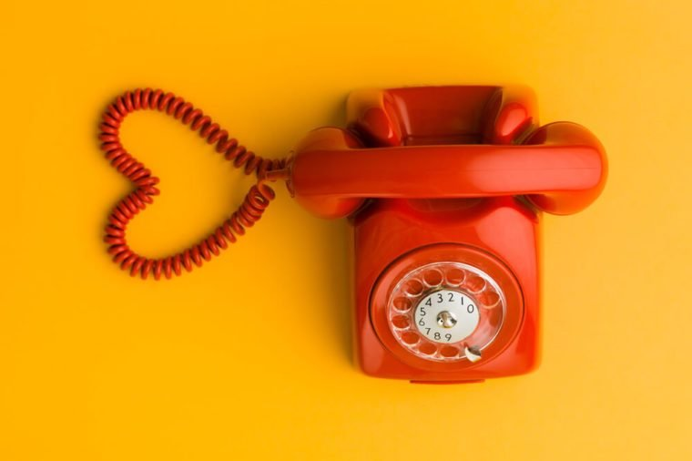 upper view of red phone with heart shape made out of its cable, on yellow background