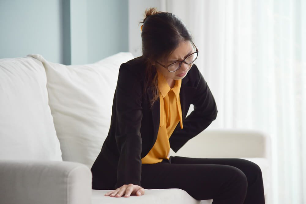 Young Asian glasses business woman sitting on sofa and suffering from stomach ache. Illness, diseases concept.