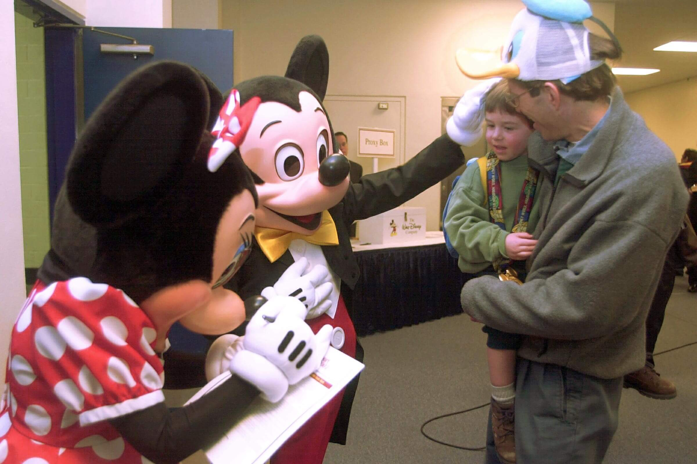 MOUSE An actor dressed as Mickey Mouse pats Michael Thramann, 3, of Avon, Conn., on the head before the start of a Disney Corp. stockholders meeting in Hartford, Conn., . Michael is held by his father, Bill Thramann, who was wearing a Donald Duck hat. At left an actress dressed as Minnie Mouse signs an autograph. Actors dressed as Disney characteres were on hand to greet Disney stockholders as they arrived for the meeting