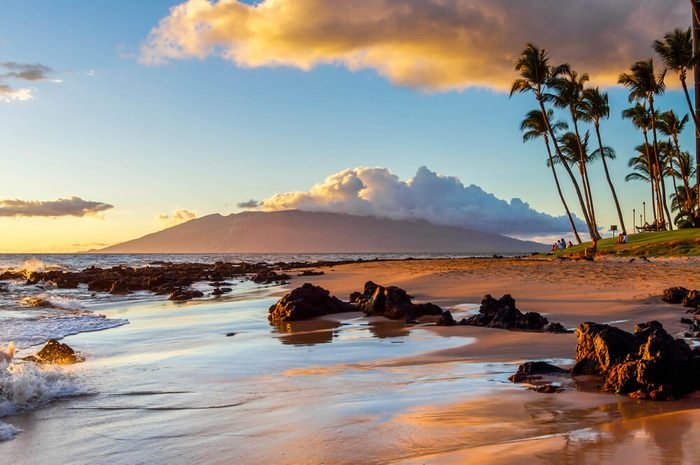 The sunset creates a warm glow on a beach in Maui.
