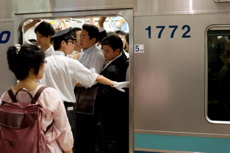 Crowds of commuters on subway tube trains in Tokyo