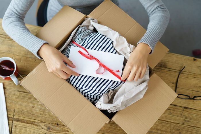 Woman packaging a Christmas gift for posting tying a red ribbon around an envelope on a giftwrapped box in a cardboard carton, high angle view