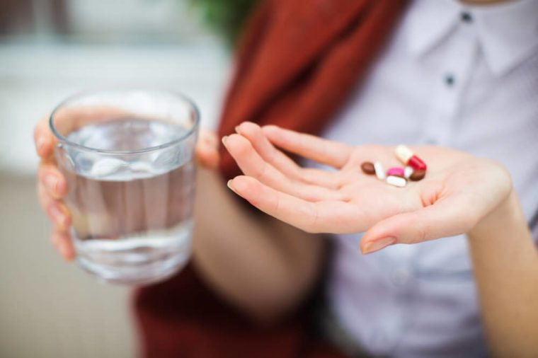 Woman hand with pills medicine tablets and glass of water