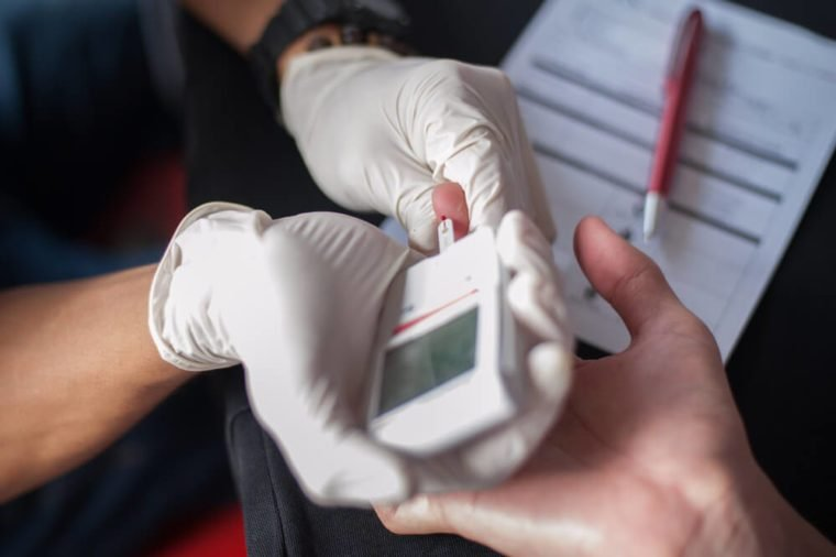 Close-up Of Doctor's Hands doing a blood test with a glucometer on the finger of a diabetes person.Close up shot with selective focus.