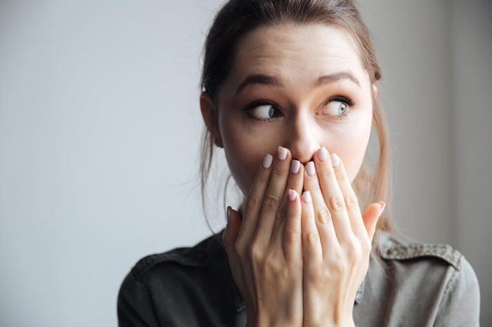 Young surprised woman in shirt looking away. covering her mouth. isolated gray background