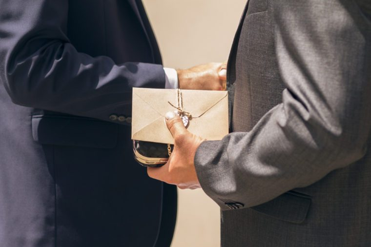 Business man giving a gift with envelope and shaking hands