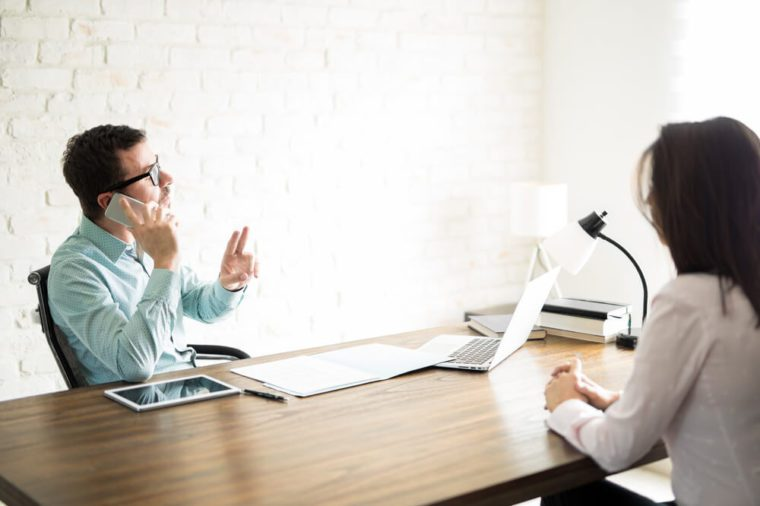 Woman sitting in an office waiting for an interview with a rude boss while he talks on the phone