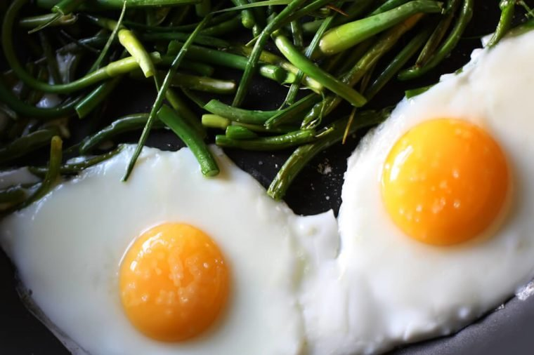 Fried eggs with green beans on the pan close up