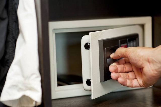 Men's hand opens a safe hidden in the wardrobe. Small home or hotel safe