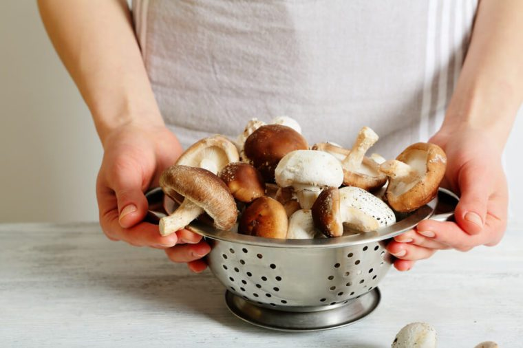 Female chef hands holding a colander with shiitake mushrooms