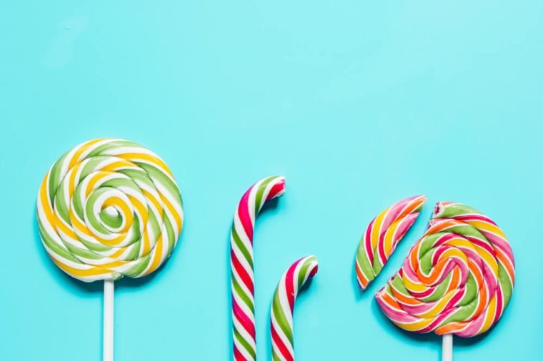 Colorful candies on blue texture background top view mock up