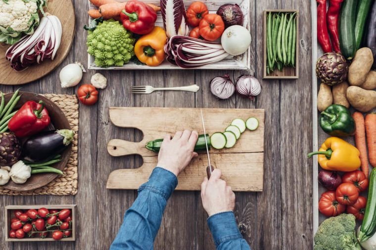 Man cooking and slicing fresh vegetables on a rustic kitchen worktop, healthy eating concept, flat lay