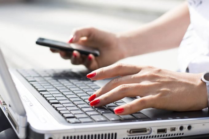 Hands of a businesswoman typing on a computer keyboard and holding phone in the other hand