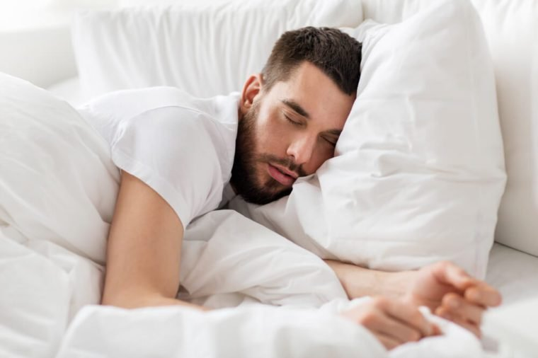 rest, bedtime and people concept- close up of man sleeping in bed at home
