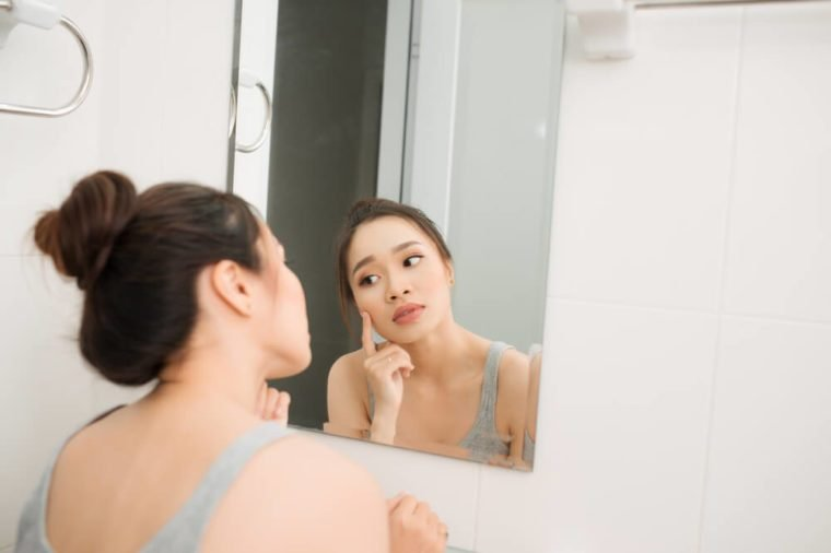 Asian woman holding a mirror, touch and worrying about her face