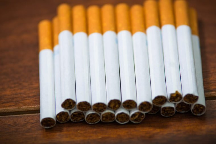 Stack of many cigarettes placed on wooden surface, as seen from above, artistic anti smoking concept