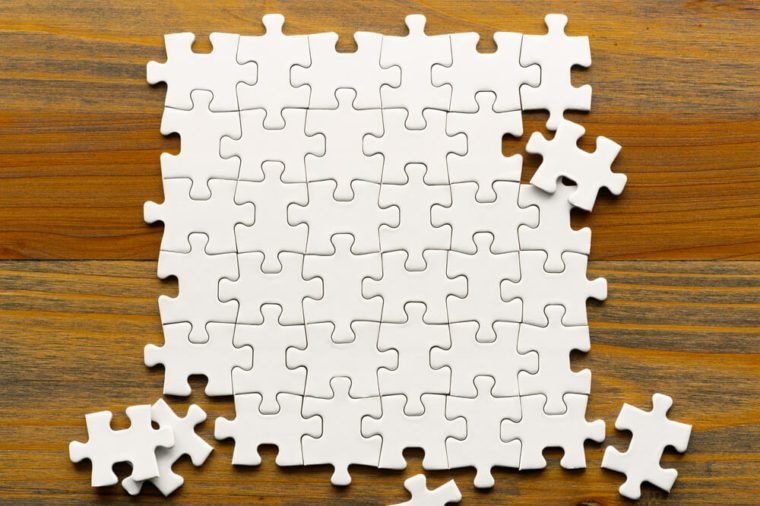White puzzle pieces on wood background. Partially completed square shaped puzzle pieces.