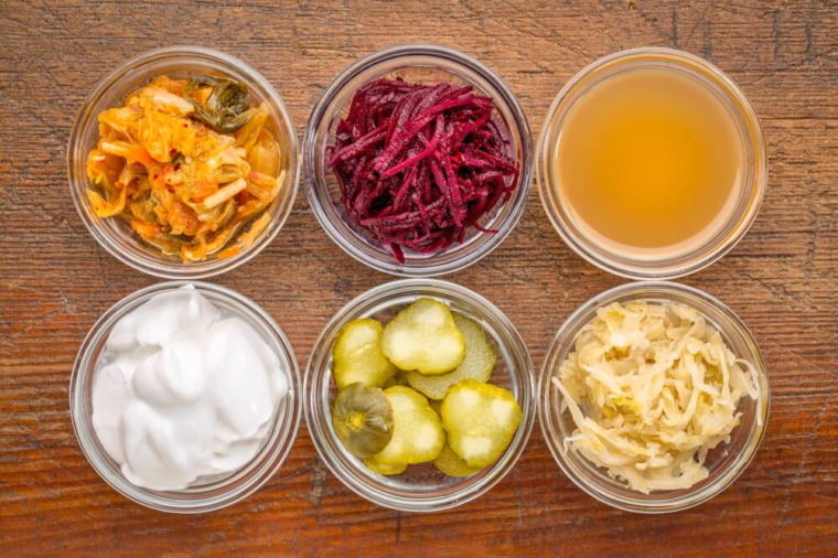 a set of fermented food great for gut health - top view of glass bowls against rustic wood: kimchi, red beets, apple cider vinegar, coconut milk yogurt, cucumber pickles, sauerkraut
