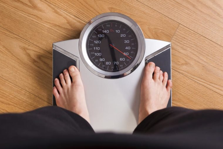 Athletic young girl measuring her weight on a scale
