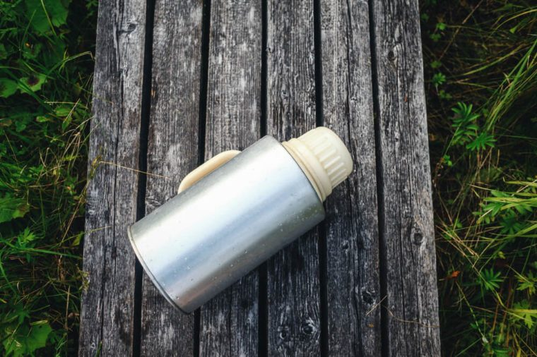 Large old thermos on the background of wooden boards