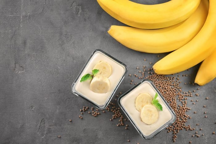 Bowls with delicious banana pudding on grey background