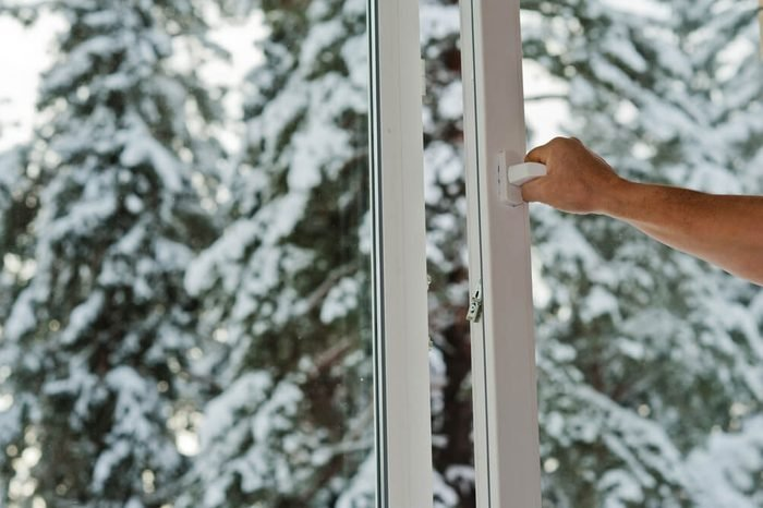 man opens the plastic window with forest view