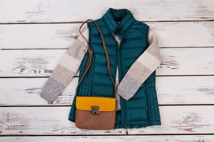 Pairing of turquoise vest and brown bag. Stylish layering of clothing for winter season. Women's fashion.