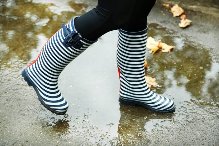 Woman in Boots on rainy autumn day.