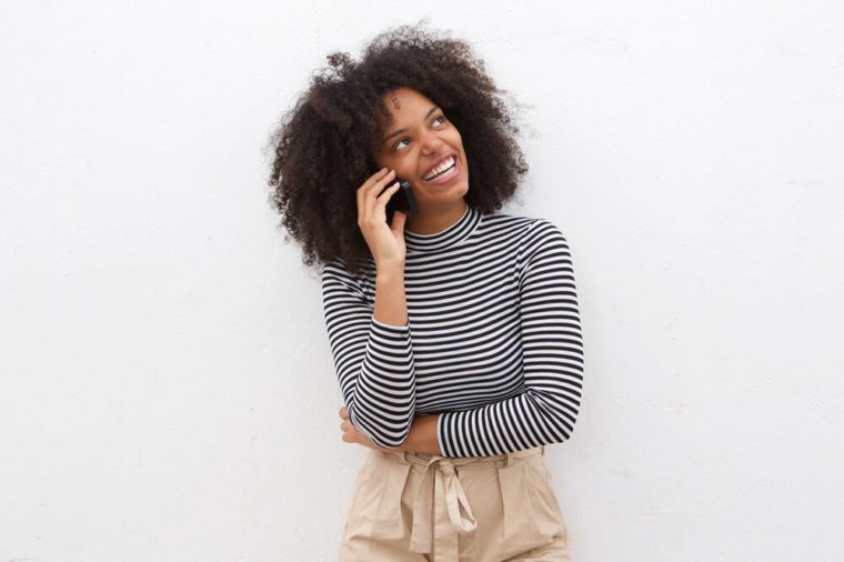 Portrait of happy black woman talking on mobile phone