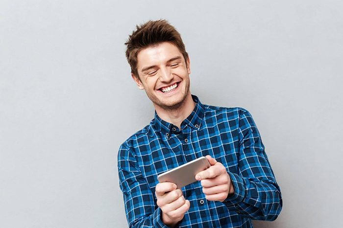 Funny man laughing while playing with smartphone isolated