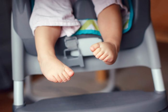 Closeup of adorable chubby baby legs feet. Small kid sitting in high chair. Macro detail of cute child