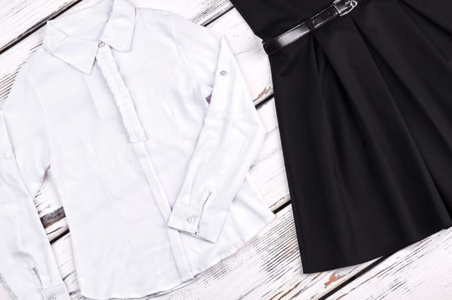 Girls school clothes, wooden background. White cotton shirt and black dress for school wear. Traditional school clothes for girls.