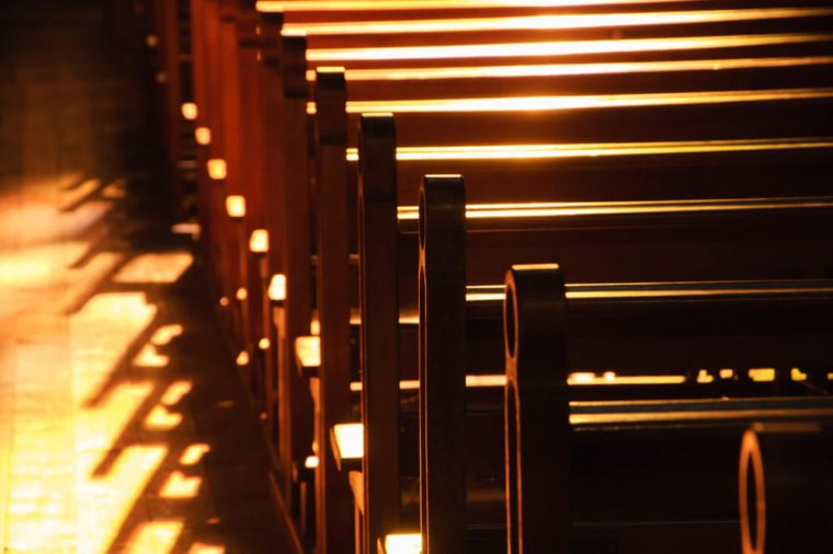 Rows of church benches. Sunlight filtered through the stained glass window. Selective focus. Black and white.