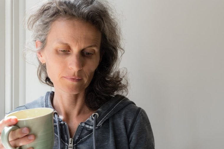 Middle aged woman with grey hair holding green cup and looking pensive.