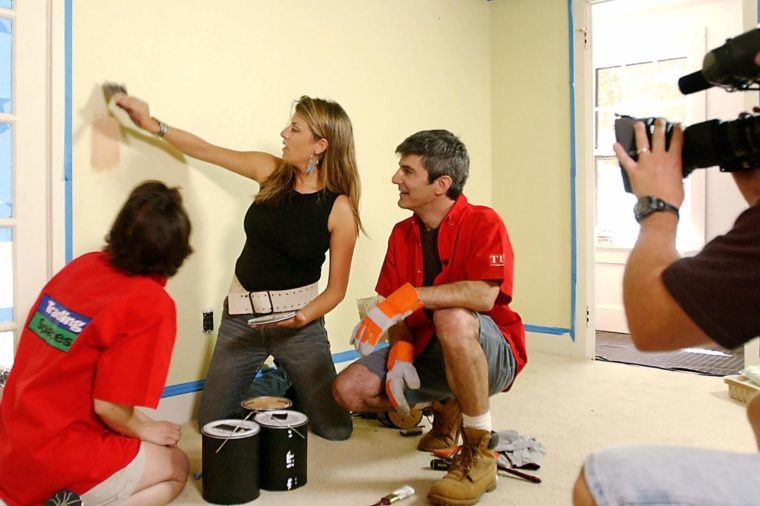 "GORDER MINASIAN Designer Genevieve Gorder, center, shows home-owner participants Amy Minasian, left, and husband Phil the color of the paint she plans to use as a cameraman tapes TLC's ""Trading Spaces"" in Katonah, N.Y., . A mix of a reality and game show, the series takes neighbors who agree, with a professional designer's help, to make over a room in the other's home"
