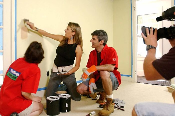 """GORDER MINASIAN Designer Genevieve Gorder, center, shows home-owner participants Amy Minasian, left, and husband Phil the color of the paint she plans to use as a cameraman tapes TLC's """"Trading Spaces"""" in Katonah, N.Y., . A mix of a reality and game show, the series takes neighbors who agree, with a professional designer's help, to make over a room in the other's home"""