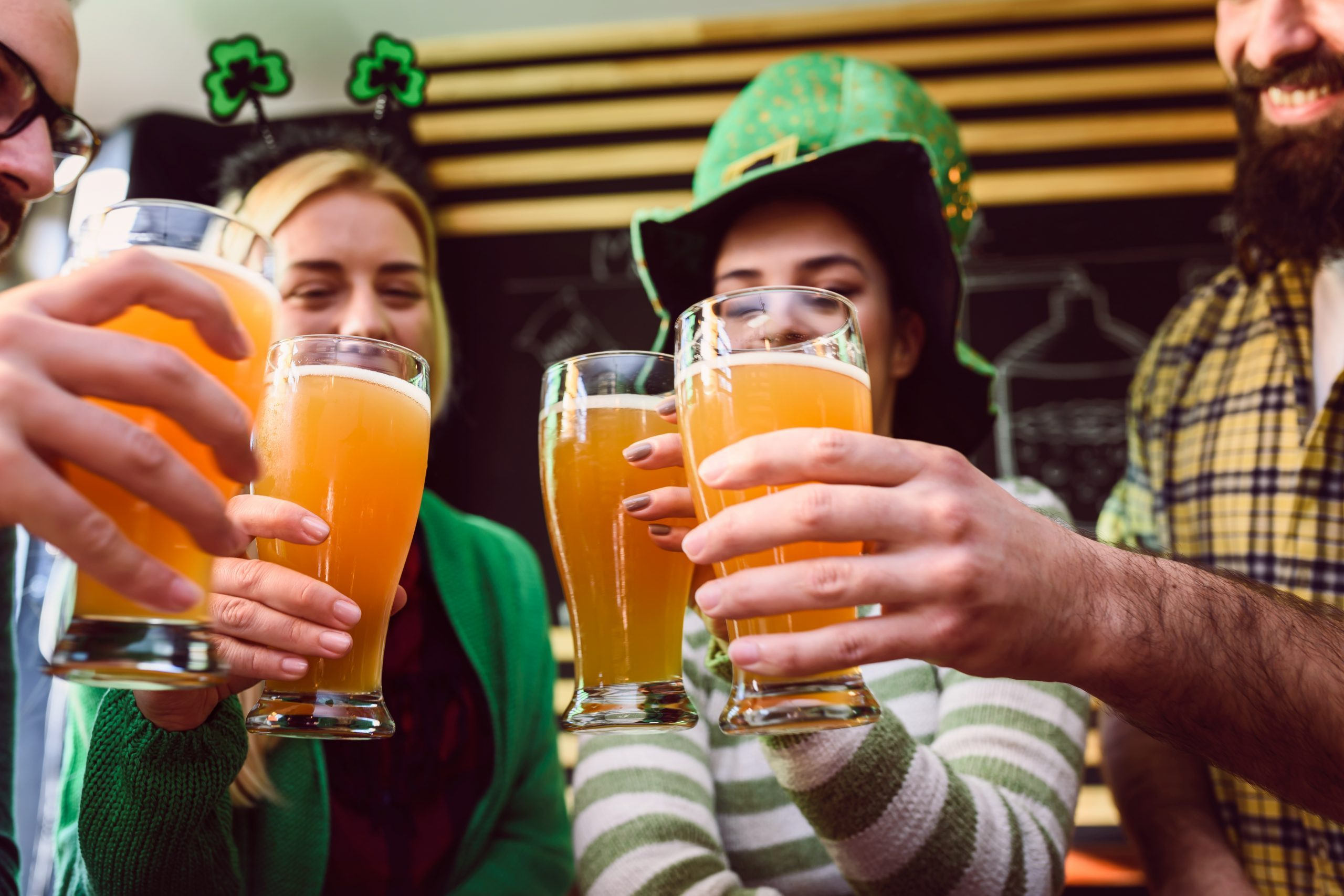 Smiling young people drinking craft beer in pub on St Patrick's Day holiday. fun facts.