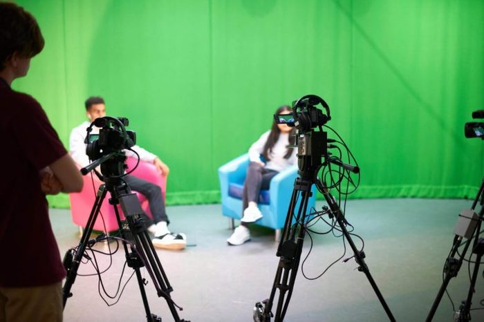 MODEL RELEASED, Young male and female college students practicing in TV studio with green screen